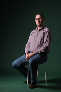 James Field Counsellor in Exeter sitting on a stool against a dark green background