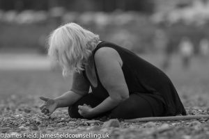 emotional image of woman in black with grey hair sitting on a beach